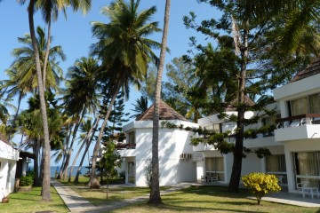 Garten mit Blick zum Meer und den Zimmern im Kenya Bay Beach Hotel