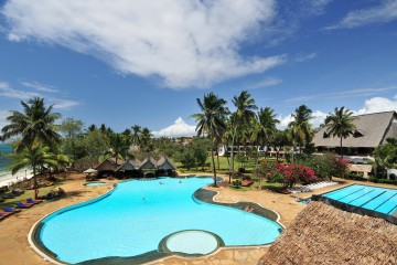 Blick über Pool- und Gartenlandschaft zum Strand im Hotel The Reef